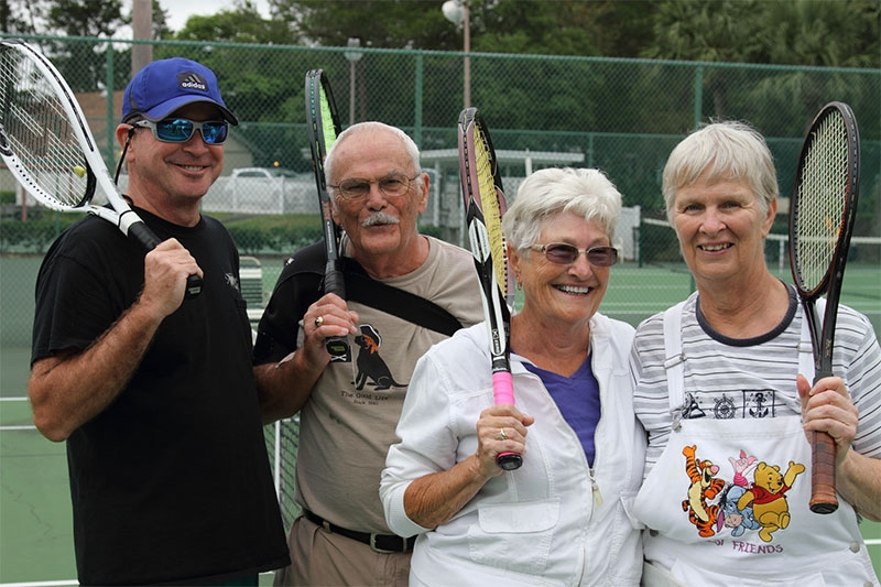 Group of four tennis players on tennis court