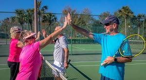 Couples slap hands over tennis net